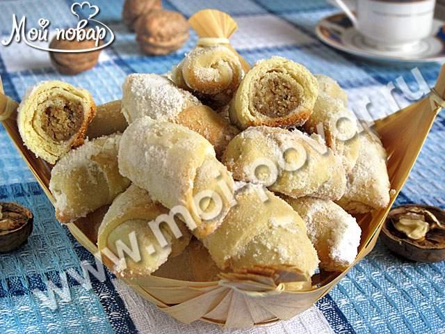 Рогалики из песочного теста с ореховой начинкой. Ингредиенты: Мука-400г. Сливочное масло-200г. Сметана-200г. Яйца-1шт. Сахар-100г. Ванильный сахар-2ч.л. Разрыхлитель для теста-2ч.л. (или 1ч.л. гашеной соды). Сахарная пудра-6ст.л. (или по вкусу). Для начинки: Грецкие орехи-300г.(очищенные) Сахар-5ст.л.